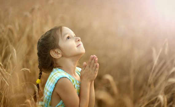 Cute happy little girl prays in wheat field