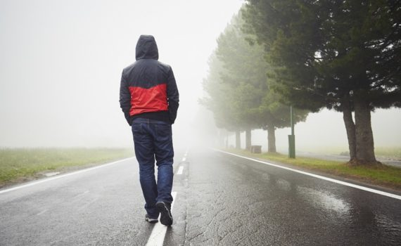 Lonely man is walking in mysterious fog